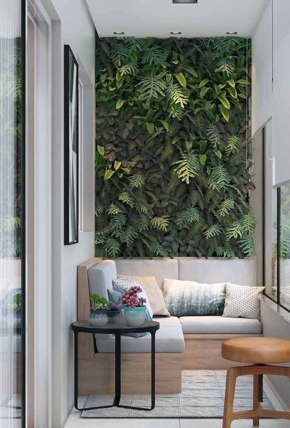 Forração verde na parede da varanda; para contemplar esse espaço invista em um sofazinho ou em puffs