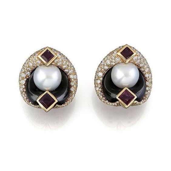 MARINA B. <br>  <br> Une paire de clip d'oreille en or jaune (18K, 750‰) et acier noirci orné en son centre d'une importante perle de…