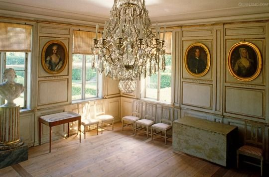 glt-framed oval ancestral portraits hang on the panelled walls of this salon, red gingham blinds dress the windows with a crystal chandelier