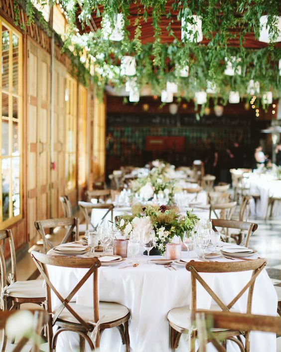 The reception took place in the property's Apple House, a narrow wooden building with quirky black-and-white tiled floors. Staying true to the wedding's simple, rustic look, Natalie, surprised the newlyweds with hanging greenery (a mix of smilax and dee brush) to complement the existing lanterns. To accommodate everyone, they had a mix of long and round tables, finished off with white linens and cross-backed wooden chairs.