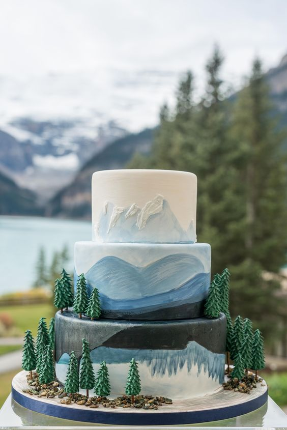 Fun, Canadiana style, nature inspired wedding cake with trees and blue hand painted mountains at Lake Louise. Photo by one-edition.ca, cake by Cake Sensations.