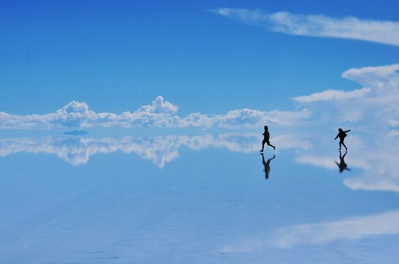 14 Surreal Places You Have to Visit Before You Die -- Salar De Uyuni in Bolivia -- This natural wonder is the largest salt flat in the world. During the rainy season, it is covered by a thin layer of water, turning the flat into a giant mirror.(in photo)