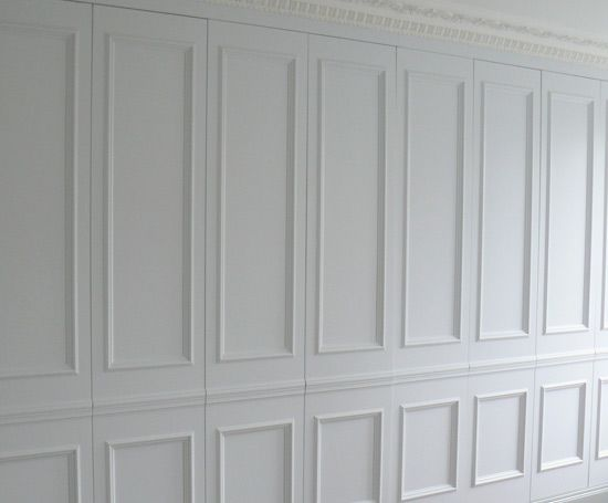 What looks like traditional panelling is actually a series of wardrobe doors that conceal a variety of storage [see next].