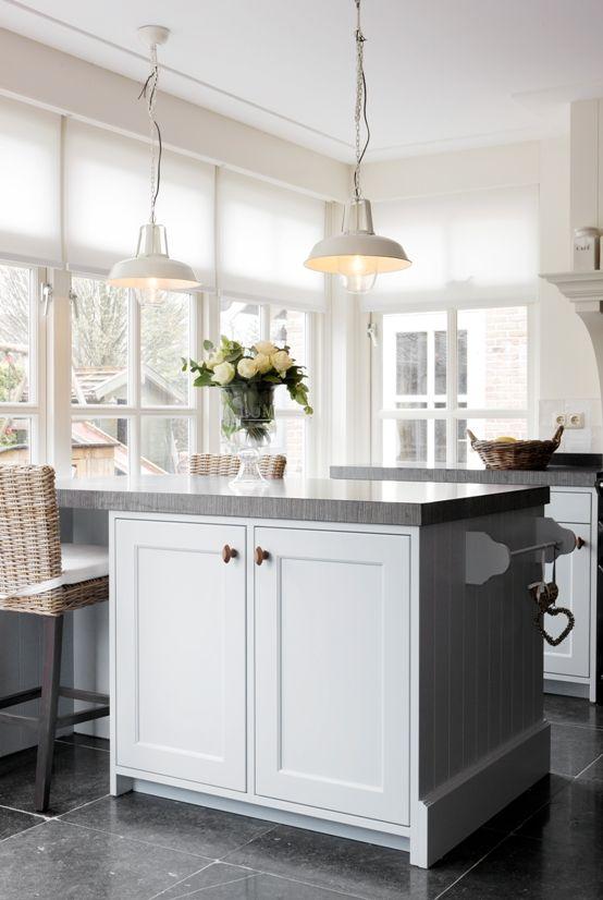 Landelijke, witte keuken met kaderdeuren en o.a. een zwart fornuis ...