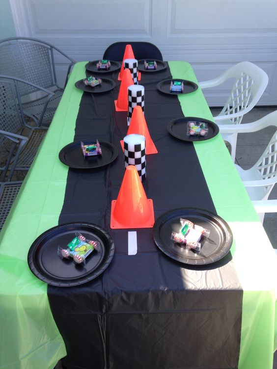 Use black tablecover with white tape as street lines and cones as part of table decorations.