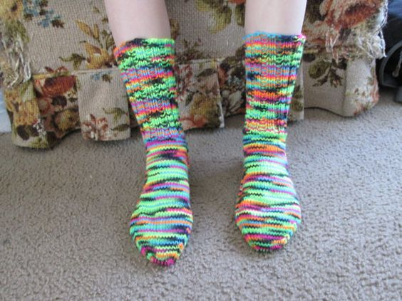Here is a wonderful pair of hand knit adult size socks. The color is called Blacklight. Heel to toe is approx. 9 1/2 in. and the ribbing on the top (top to ankle) is approx. 6 1/2 in. These socks are made of 100% acrylic yarn and can be machine washed and dried.