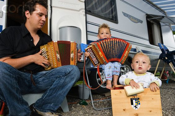"""""""Yeniche Jean-Noel Birchler plays the accordion with his sons in front of his trailer in Liestal in the demicanton of Basel-Landschaft, Switzerland. The Yeniche, or Jenische, are the third-largest population of nomadic people (or """"Travelers"""") in Europe, living mostly in Germany, Austria, Switzerland, and parts of France. They are some of the most geographically widespread in Western Europe."""":"""