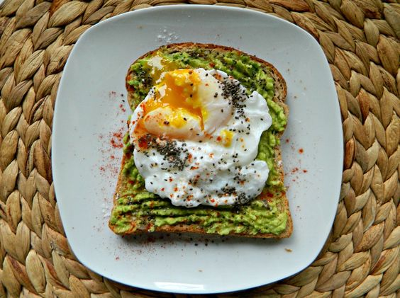 Slice of multi-grain toast with mashed avocado, fried egg, cayenne, paprika and chia seeds