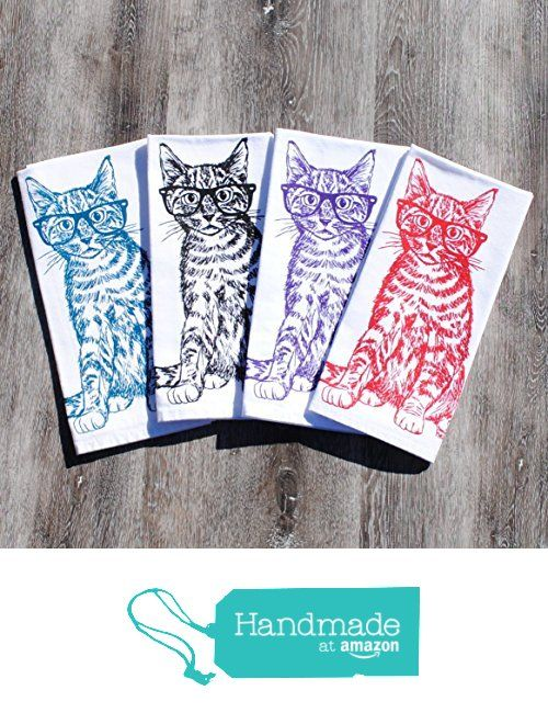 Four cotton napkins on a wooden table. Printed with cats with glasses, in four colours blue, black, violet and red.