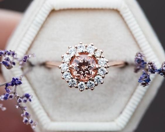 A new take on a vintage inspired cluster ring. This ring is unique and super sparkly! Ring details- -Main stone is a 6mm Chatham made peach sapphire, certification included. -Halo surrounding the stones are 2mm forever one colorless moissanite. -One stone is a 2mm champagne diamond. -Cast in your