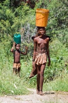 Young Himba woman carries a bucket, Namibia Stock Photo