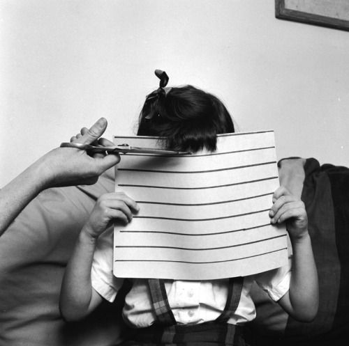 A young girl holds up a piece of cardboard to ensure that her mother cuts her fringe straight, circa 1955. Photo by Sherman/Three Lions/Getty Images