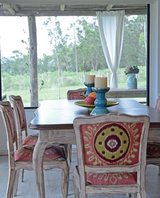 En el comedor, la mesa y las sillas de cedro revivieron con el reciclaje realizado por Bernardita O.: pátina beige para las maderas y tapizado de mandalas en coral, verde agua y turquesa. Los candelabros de cerámica turquesa, el plato de bambú verde y los tonos vibrantes de las esferas suman chispazos de color.
