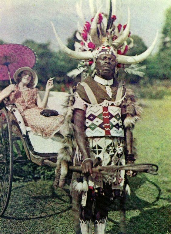 A Zulu tribesman pulling his female employer around in a rickshaw. Durban, South Africa, 1930s.