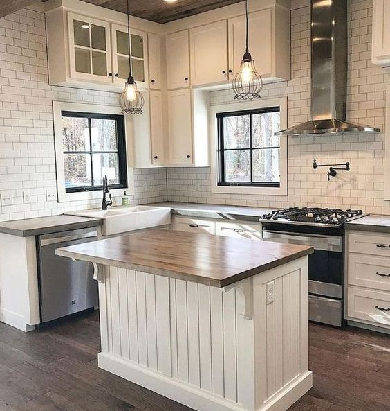 White modern farmhouse kitchen with subway tile, beadboard, and wood top island. #modernfarmhouse #kitchen #whitekitchen #blackandwhite