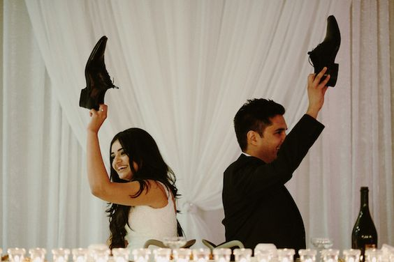 Who's more romantic? bride and groom hold up shoes to represent their answers