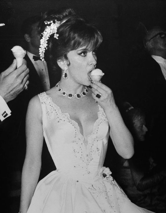 Italian actress Gina Lollobrigida eating ice cream at the Monaco Centenary Ball, 1966.