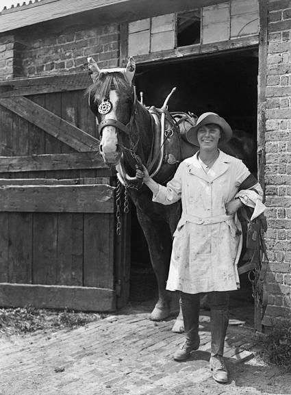A member of the Women's Land Army leads a horse from the stables on a farm during the First World War