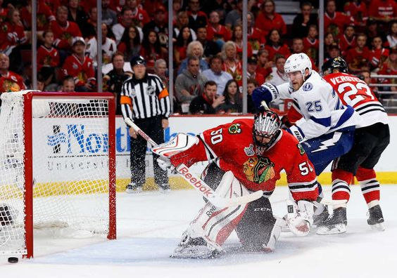 CHICAGO, IL - JUNE 15: Matt Carle #25 of the Tampa Bay Lightning watches as goaltender Corey Crawford #50 of the Chicago Blackhawks defends the net on a shot during the first period of Game Six of the 2015 NHL Stanley Cup Final at the United Center on June 15, 2015 in Chicago, Illinois. (Photo by Scott Audette/NHLI via Getty Images)