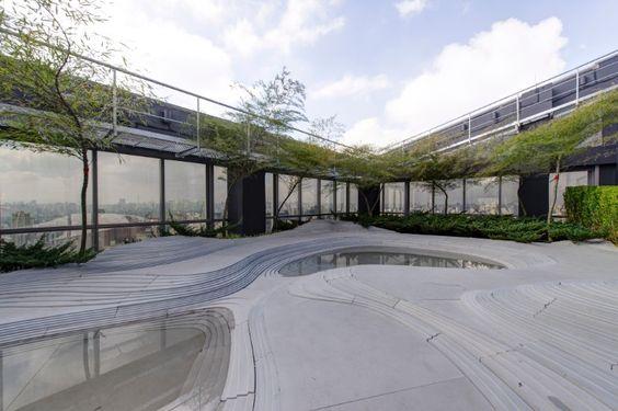 """As curvas suaves da instalação """"Stonescape"""" do arquiteto japonês Kengo Kuma, produzida em conjunto com a empresa italiana II Casone, dão forma escultural ao ambiente de 190 m² do paisagista Gilberto Elkis, na cobertura do prédio. 3ª Mostra Black - São Paulo"""