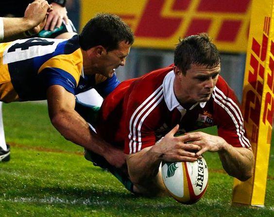 Biran O'Driscoll, dos Lions britânicos, falha o ensaio por muito pouco, devido à placagem 'in extremis' de Alex Gibbon, durante um jogo da Rugby Union, em Newcastle. (© © REUTERS / Daniel Munoz)