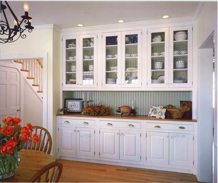 Light blue beadboard backsplash with white cabinets and (what looks like) butcher block countertops.