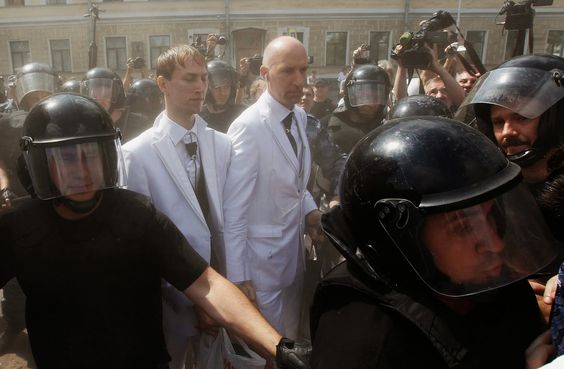 Russian same-sex couple Yury Gavrikov (center R) and Maxim Lysak (center L), surrounded by riot police officers, arrive at a Gay Pride event in St. Petersburg, June 29, 2013. Dozens of gay and lesbian rights activists and their supporters gahtered for the event but were attacked by anti-gay protesters and later dispersed by the police.  REUTERS/Alexander Demianchuk (RUSSIA - Tags: SOCIETY CIVIL UNREST)