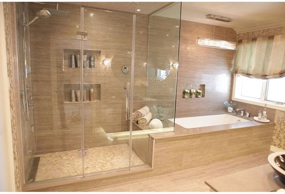 A shower with glass doors chandelier above the bathtub for Spa inspired bedroom designs