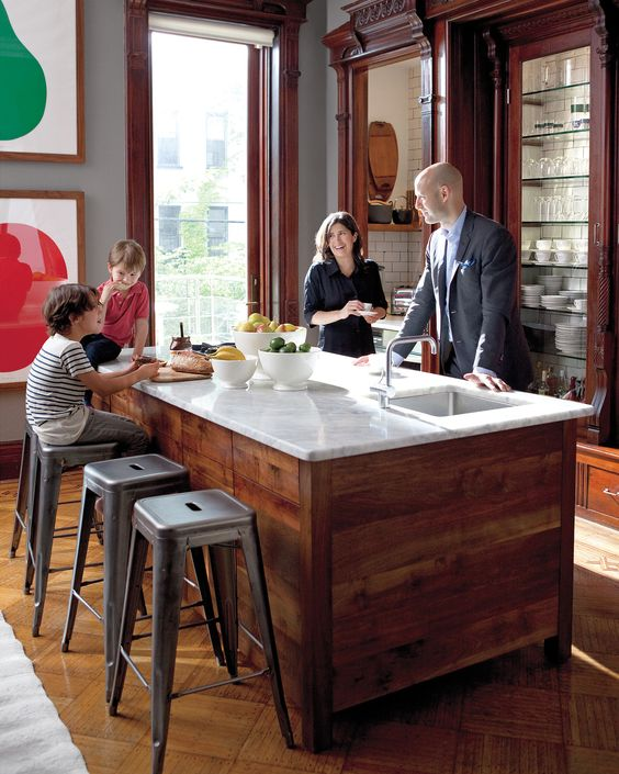 "Martha Stewart Living editor in chief Pilar Guzman; her husband, Chris Mitchell; and their two boys, Willem and Henry, gather in the kitchen of their Brooklyn brownstone. ""We spend about 80 percent of our time here,"" Pilar says. The couple retrofitted the room, which was originally a formal parlor, as a kitchen; former closets house appliances and dishes, and a marble-top island was built by designer Tyler Hays."