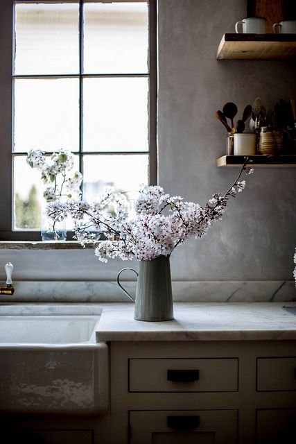 See more of the inspiring kitchen decor and kitchen ideas in Beth Kirby's kitchen. Lovely cherry blossoms in a pitcher on the counter near rustic open shelves. #modernfarmhouse #kitchendecor #kitchenideas #bethkirby #rusticdecor #cherryblossoms
