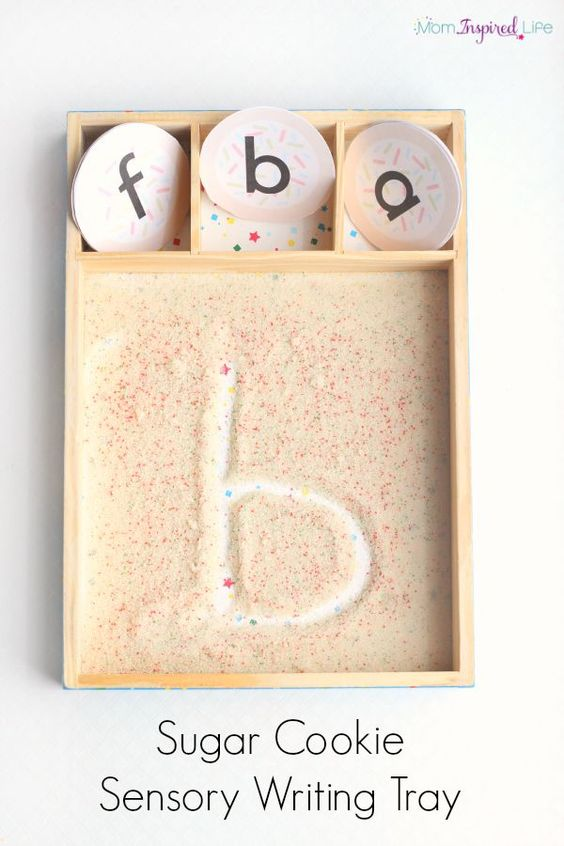 Learning to write letters with a sugar cookie sensory tray! This is such a fun way to use your senses to learn the alphabet. This would make a great Christmas sensory writing activity!
