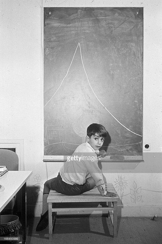 Cyrus Reza. Téhéran-30 octobre 1967- Portrait du prince Reza Cyrus PAHLAVI, fils du Shah et de Farah DIBA, assis sur un tabouret devant un grand tableau noir, dans sa chambre.