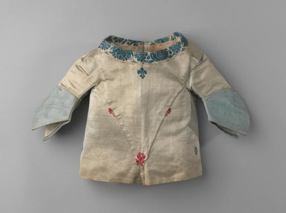 Infant's jacket, probably for a boy, 1740-1770. White silk satin brocaded with red and blue flowers, trimmed with silk ribbon, white linen lining.