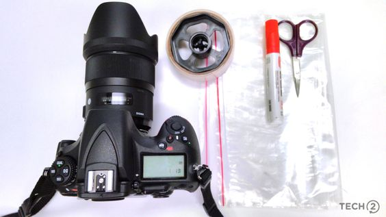 You will need your DSLR with lens and hood, a pair of scissors, cellotape, marker and a transparent zip-lock bag