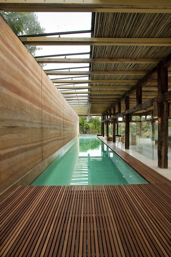 indoor lap pool with rammed earth wall at the dalrymple