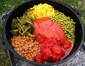Dutch Oven Cowboy Stew.  Super easy, because most of it comes from cans.  Here I dumped in corn, peas, green beans, pork and beans, tomatoes and tomato soup.  Getting ready to mix it all up and get it cooking!