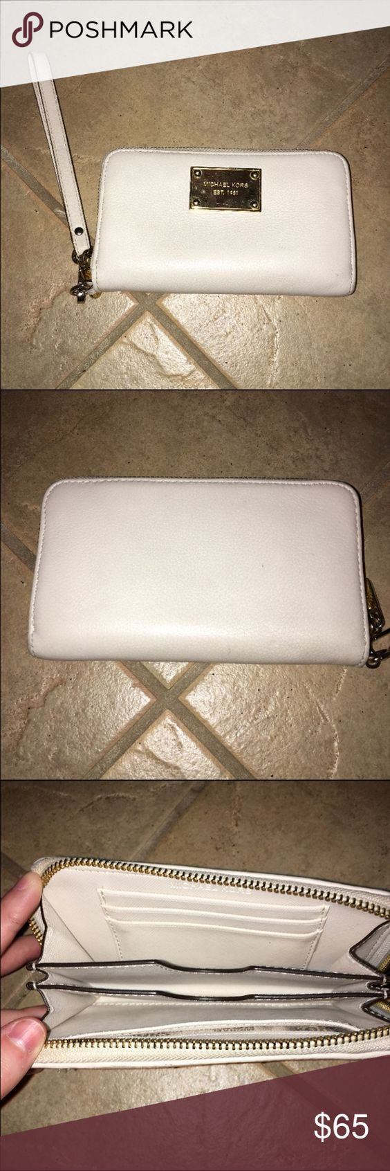 Michael Kors white wallet w/ wrist strap Michael Kors white wallet w/ wrist strap Authentic MK White wallet  Lightly used still in great condition 7 in X 4 in X 1 in Michael Kors Bags Wallets
