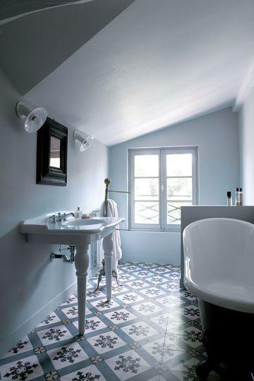 Dans la salle de bains dédiée aux enfants, on retrouve de la réédition avec un lavabo en porcelaine blanche et une baignoire tête de lion. Le carreau de ciment se marie aux teintes pastel des murs.