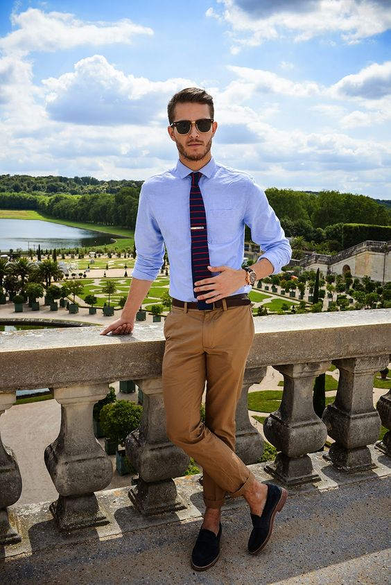Shop this look on Lookastic: http://lookastic.com/men/looks/sunglasses-dress-shirt-tie-belt-chinos-loafers/8617 — Dark Brown Sunglasses — Light Blue Dress Shirt — Navy Horizontal Striped Tie — Dark Brown Leather Belt — Brown Chinos — Black Suede Loafers