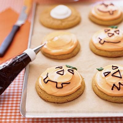 Jack-o'-lantern Cookies: Use black icing to pipe a design onto these frosted pumpkin cookies.