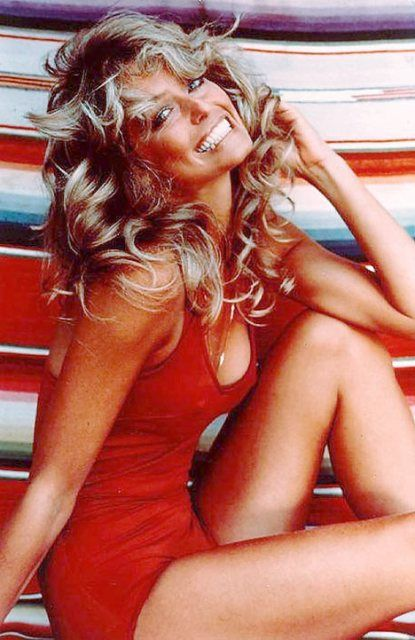 Farrah Fawcett is perfection in this classic red swimsuit and feathered hair