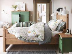Un dormitorio verde con cama HURDAL de madera maciza, ropa de cama estampada SISSELA y solución de almacenaje HURDAL