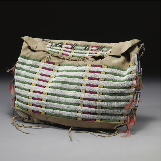 A LAKOTA BEADED HIDE POSSIBLE BAG composed of hide, glass beads, tin co...