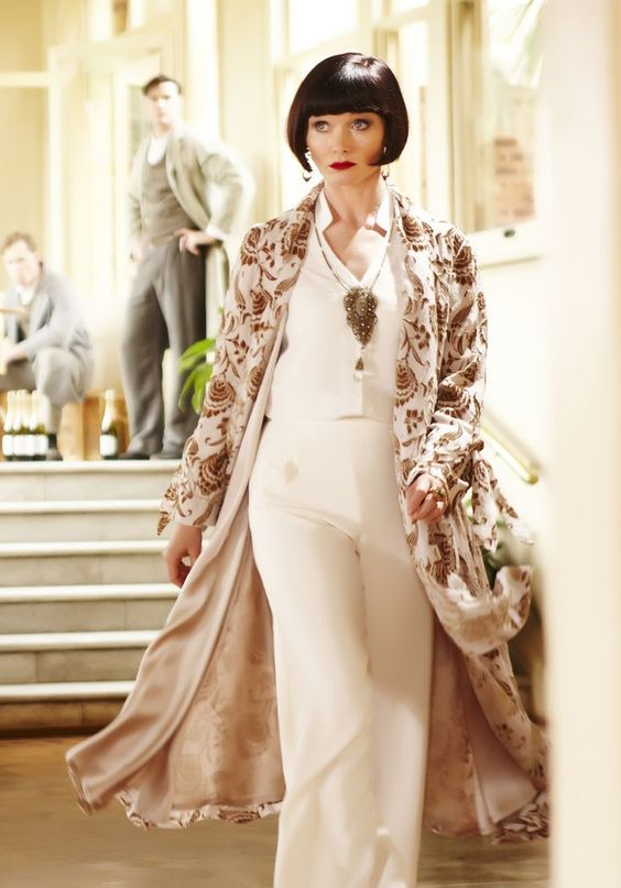 Miss Fisher wearing all white and a long coat from Miss Fisher's Murder Mystery
