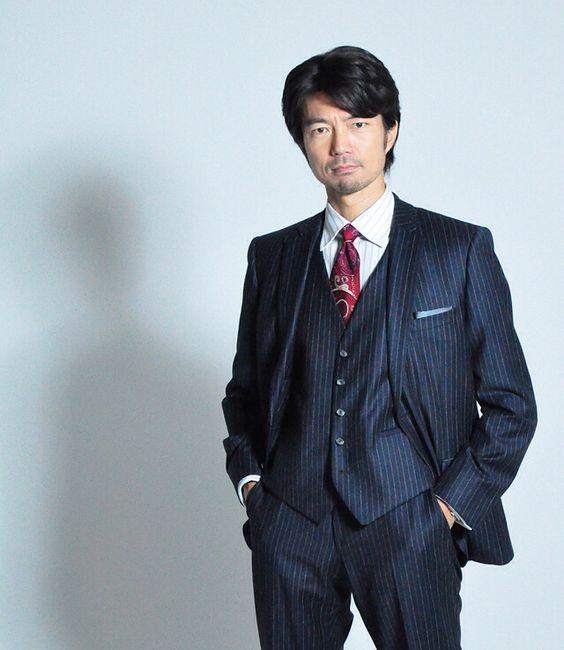 スーツに赤の派手のネクタイ姿の仲村トオル