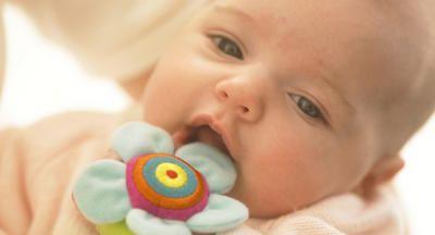 Bebé con sonaja de tela atada en la mano