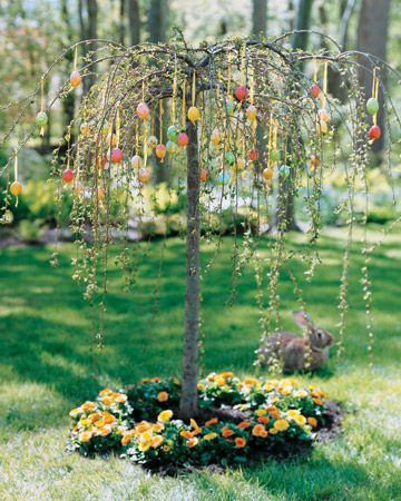 Easter decorations in the garden /  Colorful Egg Tree    Every passerby, including a wayfaring rabbit, stops to admire this weeping cherry tree. With bright marbleized eggs suspended on yellow ribbons and a ring of golden pot marigolds around the base, it sets the stage for a lively egg hunt or leisurely spring brunch.