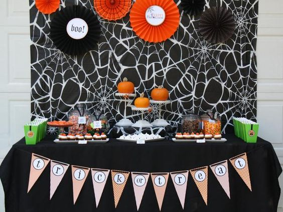 Halloween Table Settings and Decorations: Set a playful spider web tablecloth as the backdrop and enhanced it with inexpensive paper Halloween fans. Put the pumpkins on cake stands to make them the focal point of the table.  #Halloween #crafts #party