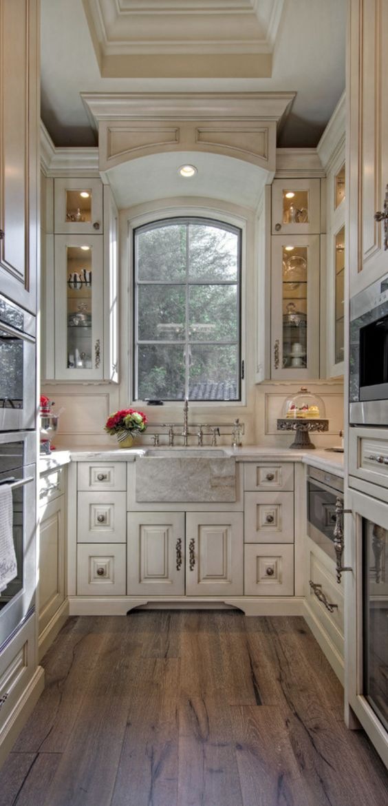 Beautiful galley kitchen takes advantage of vertical space with beautiful traditional cabinetry. Stone farm sink and wood flooring add warmth and charm. #smallkitchen #ushaped #archwindow #stonesink