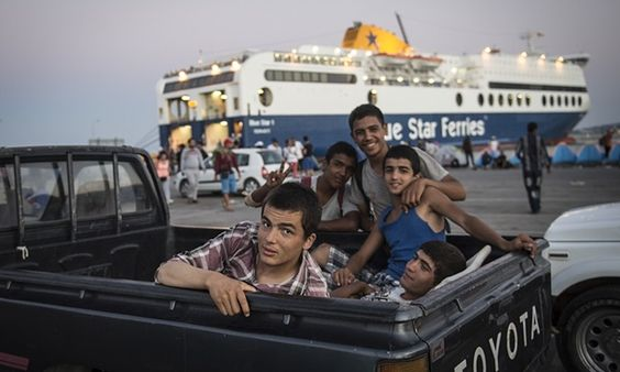 Refugees who took a boat from Turkey to Lesbos Island are seen behind a vehicle as they wait at a port to get a ferryboat to go to Athens.